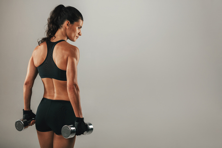 pony tail: Rear three quarter view of beautiful female bodybuilder with pony tail and black outfit Stock Photo