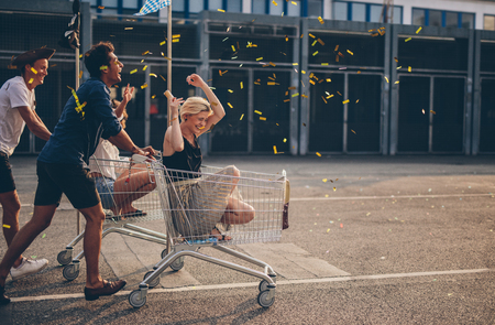 lot of: Multiethnic young people racing with shopping cart and blowing confetti. Young friends having fun on shopping carts. Stock Photo