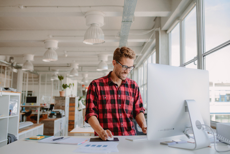 Shot of szczęśliwy młody człowiek pracy na komputerze stacjonarnym w nowoczesnym miejscu pracy. Młody przedsiębiorca pracujący przy starcie. Zdjęcie Seryjne