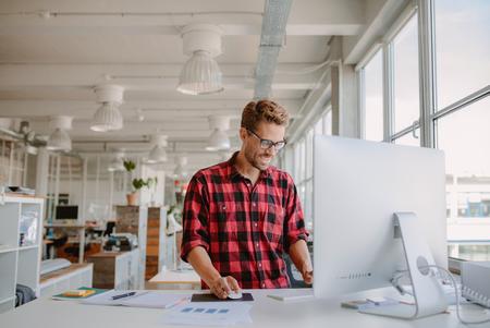 Shot von glücklichen jungen Mann arbeitet auf Desktop-Computer in modernen Arbeitsplatz. Jungunternehmer arbeiten bei der Inbetriebnahme.