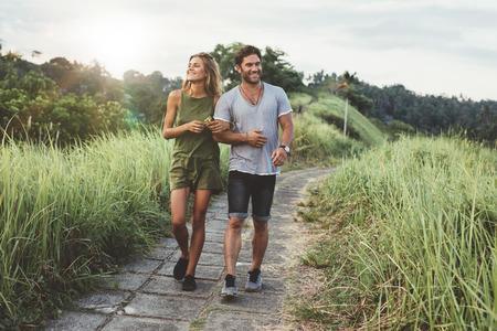 Buiten schot van de jonge paar in liefde wandelen op de weg door het gras veld. Man en vrouw lopen langs het hoge gras veld. Stockfoto