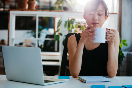 Retrato de mujer joven relajada, sentado en su escritorio y tomar un café. Mujer de negocios asiática que toma el descanso para tomar café en oficina. Foto de archivo - 64921097