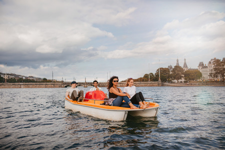 pedaling: Shot of four young people on pedal boat in lake. Women sitting on front with men at back pedaling the boat.