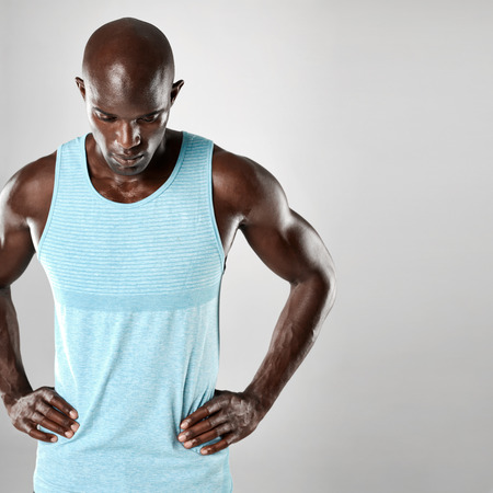 bald head: Handsome young african man with bald head and muscular arms looking downward over grey background. Stock Photo