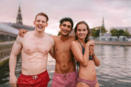 niño sin camisa: Portrait of young people in swimwear standing by a lake and looking at camera. Men in swimming trunks and woman wearing bikini standing together. Foto de archivo