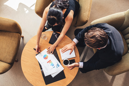 two on top: Overhead view of young businessman and woman working on graphs while sitting at office lobby. Corporate people discussing new business project using charts.