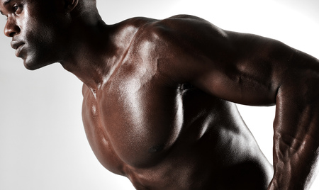 masculine: Close up of masculine young african male model against grey background. Bodybuilder with muscular physique. Stock Photo