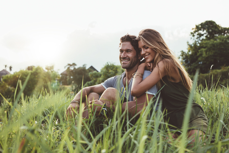 Outdoor shot of young happy lovers sitting on meadow. Happy young couple in grass. Banque d'images
