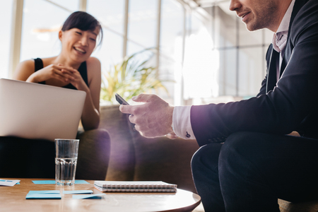 phone business: Young business man using mobile phone with woman sitting in background. Business people meeting in office lobby.