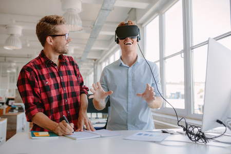 Shot of two young men testing virtual reality glasses in office. Businessman wearing VR goggles and colleague writing notes. Foto de archivo