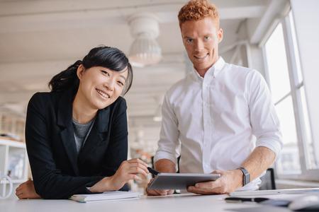 personas de pie: Retrato de socios de negocios exitosos jóvenes de pie en una mesa en la oficina con la tableta digital en la mano. Los empresarios que usa la tableta digital en la oficina. Foto de archivo