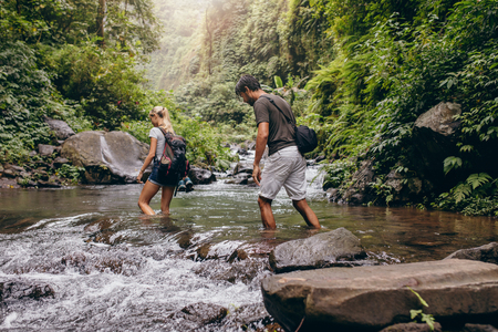 creek: Shot of young man and woman crossing a river during forest hike. Couple walking across the stream.