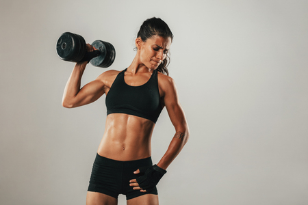 grimace: Fit strong muscular young woman holding a dumbbell aloft with a grimace and look of fierce concentration and effort