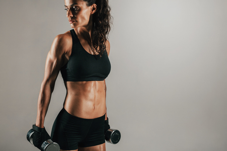 three quarter: Three quarter view on gorgeous single athletic woman resting with chrome finished dumbbell weights at her sides while looking over Stock Photo