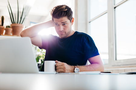 place of work: Young man holding coffee cup and looking at laptop while sitting at his desk in office. Thoughtful business man at his work place. Stock Photo