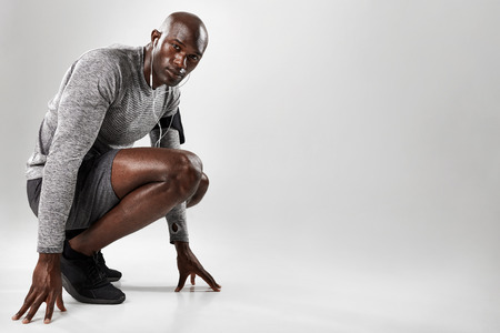 man kneeling: Portrait of healthy young black man kneeling on grey background and looking at camera with copy space.