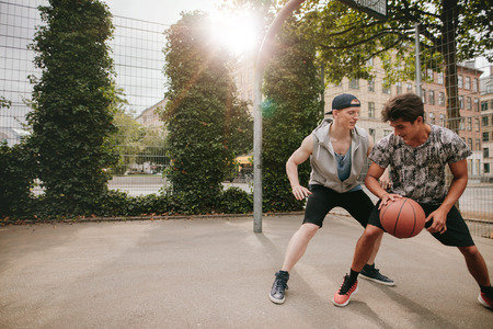 young male: Young men playing a game of basketball on an outdoor court. Teenage friends playing basketball against each other.