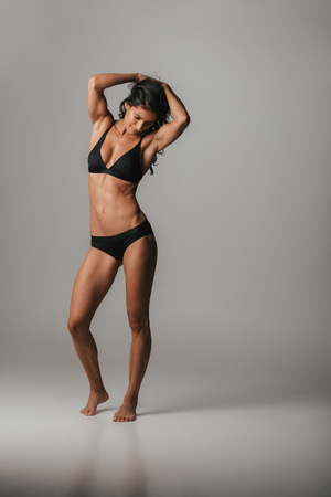 Fit graceful young woman with a toned athletic body modelling black lingerie standing with raised arms over a grey background