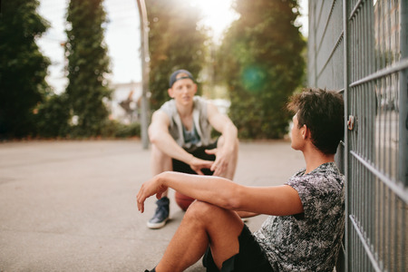 young boys: Young man relaxing on basketball court with a friend. Streetball players taking break after playing a game.