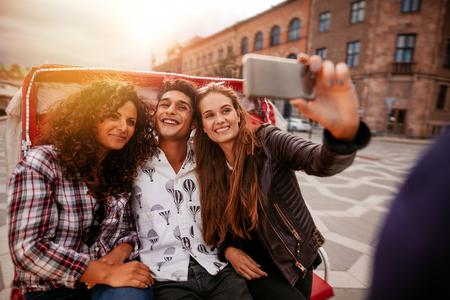 rikscha: Jugendfreunde, die selfie auf Dreirad nehmen. Junger Mann und Frauen, die auf Dreiradfahrrad fahren und Selbstporträt nehmen.