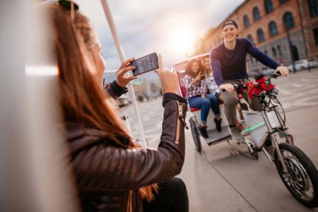 rikscha: Weiblich Fotografieren von Freunden auf Dreirad Fahrt. Freunde Urlaub genießen.