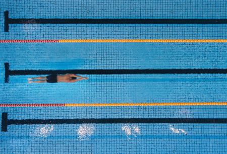 Tiro de la vista superior de las vueltas de natación del hombre joven en una piscina. Nadador de sexo masculino que se desliza a través del agua. Foto de archivo - 64925277