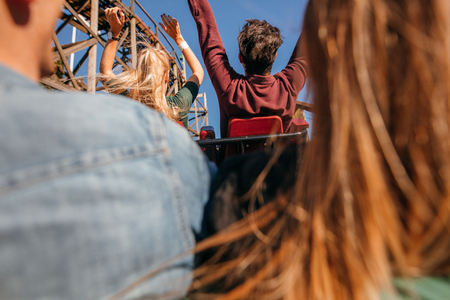 Rear view shot of young friends riding roller coaster ride at amusement park.