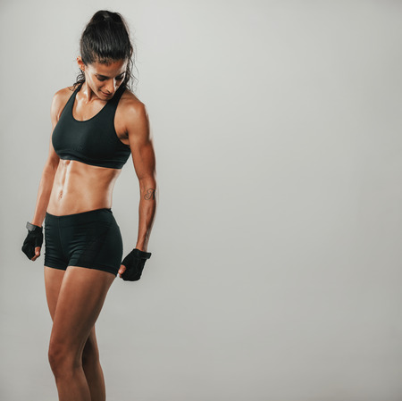 weightlifting gloves: Muscular woman in black sports shorts and top looks down while standing in a grey room