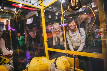 Gelukkige jonge vrouw spelen speelgoed grijpen spel met vrienden in amusement park.