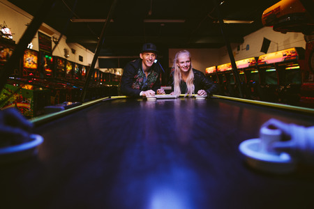 ARCADE GAMES: Young friends playing air hockey at amusement park. Man and woman playing a game of air hockey in the game room. Stock Photo