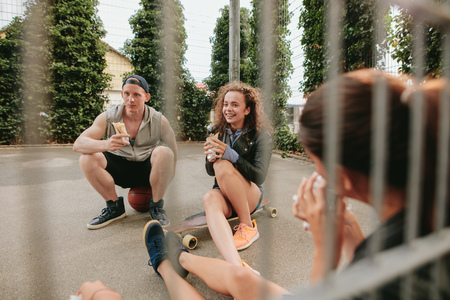 outdoor basketball court: Group of friends sitting at outdoor basketball court eating and having fun. Teenagers relaxing basketball court.