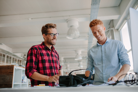 futuristic man: Shot of happy young man working together in modern office. Team of developers working on testing new virtual reality technology. Stock Photo