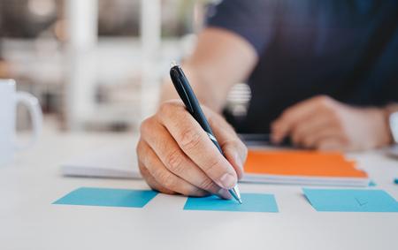 Sluit omhoog beeld van de bedrijfsmens die op een zelfklevende nota bij lijst in bureau, nadruk op hand en pen schrijven.