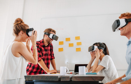 developers: Team of developers working with virtual reality glasses during a business meeting. Young business colleagues brainstorming using VR goggles. Stock Photo