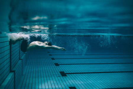 Underwater shot of male swimmer turning over in swimming pool. Pro male swimmer in action inside pool.