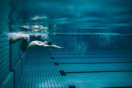 Onderwater schot van mannelijke zwemmer omdraaien in het zwembad. Pro mannelijke zwemmer in actie overdekt zwembad.