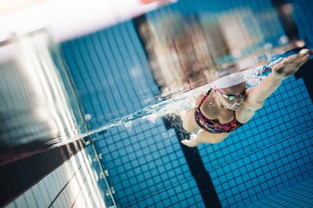Tir subaquatique d'athlète féminine nageant dans la piscine. Jeune femme nageant le style rampement avant dans une piscine. Banque d'images