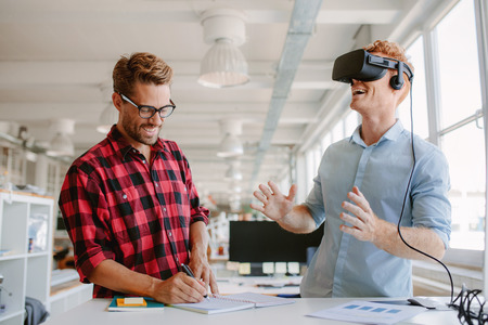 developers: Shot of two young man standing at a table with VR goggles and writing on notepad. Developers testing virtual reality glasses in office.