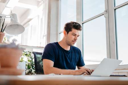 Young male executive working on laptop at his desk. Young businessman using laptop computer at work.