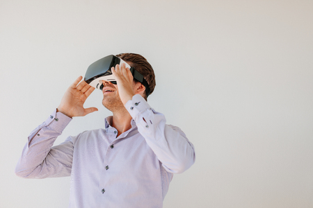 Happy young man using the virtual reality headset against grey background with copy space. Caucasian male model wearing VR goggles. Stock Photo