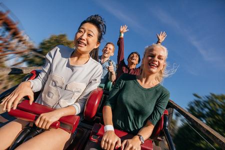 Młodzież na ekscytującą przejażdżkę kolejką górską. Grupa przyjaciół zabawy w parku rozrywki. Zdjęcie Seryjne