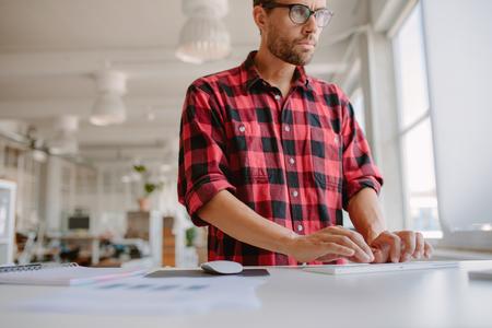 若い男が彼の机に立っていると、コンピューターで作業してのショット。近代的なオフィスのコンピューターを使用しての実業家。