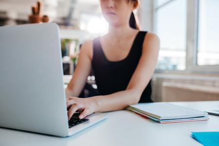 Bebouwd schot van vrouw die aan laptop op kantoor werken. Focus op handen van vrouwelijke typen op laptop toetsenbord.