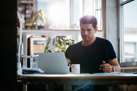 ノート パソコンを見て、メモを書く彼の机に座ってハンサムな若い男のショット。彼のオフィスで働くビジネスマン。
