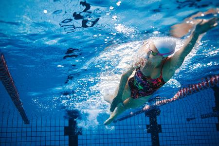 Undervattensskott av passande simmarutbildning i poolen. Kvinna simmare inuti poolen.