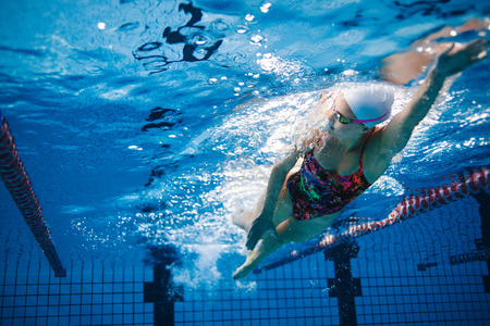 swimming race: Underwater shot of fit swimmer training in the pool. Female swimmer inside swimming pool. Stock Photo