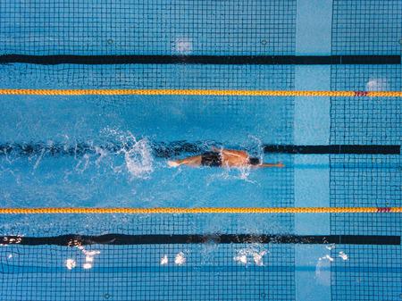 若い男がプールで水泳のトップ ビュー ショット。男性水泳プールでクロールを泳ぐします。 写真素材