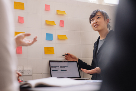 Asian businesswoman presenting her new ideas on laptop and adhesive notes on wall. Young female executive giving presentation to coworkers. Stock Photo