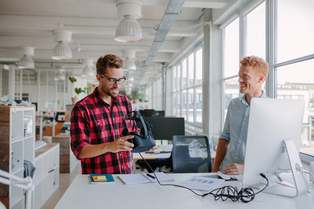 developers: Shot of two young developers testing virtual reality glasses in office. Business colleagues working in modern office, standing at a table with computer and holding VR goggles.