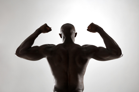 masculine: Strong back of a black muscular man flexing his arms against grey background. Rear view of african fitness model with masculine physique in silhouette.
